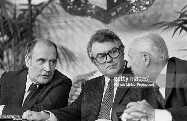 Leader of the French Socialist Party Francois Mitterrand Mayor of Lille Pierre Mauroy and Mayor of Marseille Gaston Deferre converse at a meeting The...