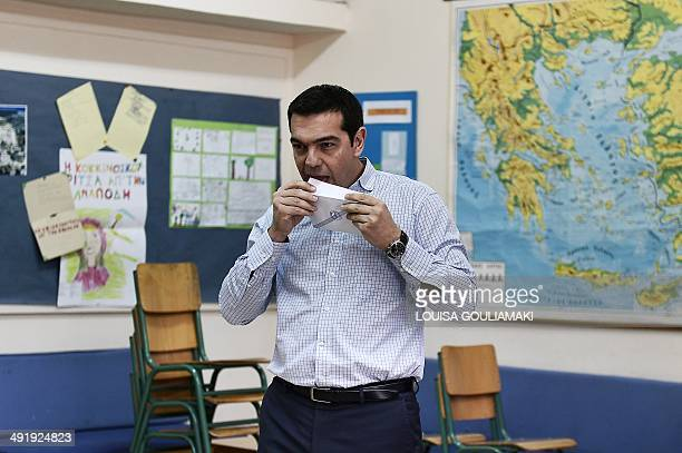 Leader of the Greek radical left party Syriza Alexis Tsipras licks his balllot envelope prior to casting his vote in a polling station in Athens on...