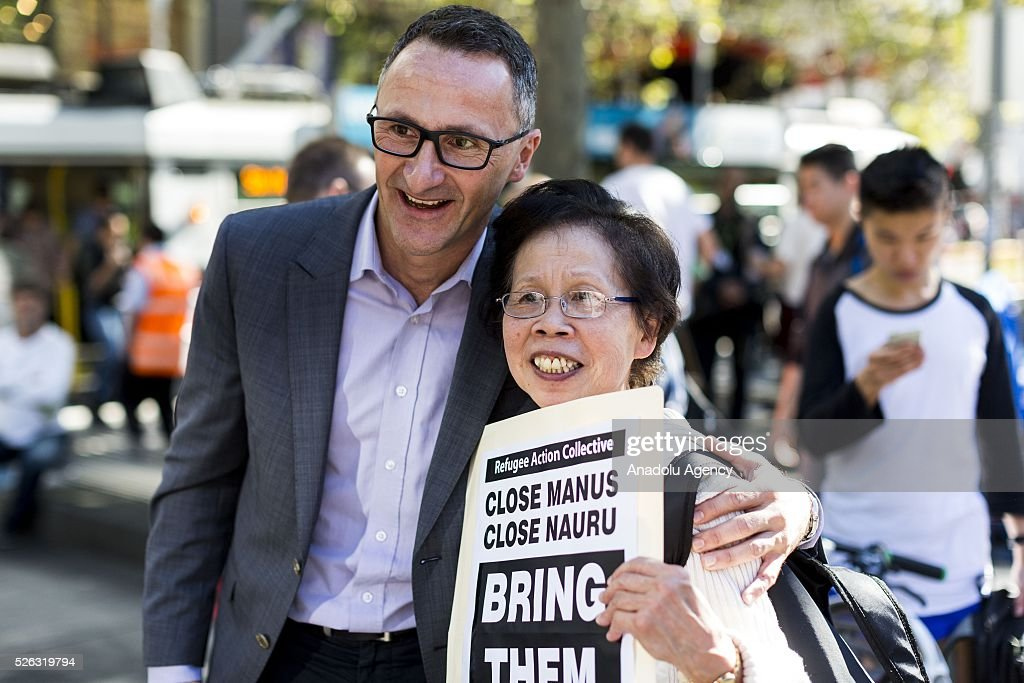 Leader of the Greens party and senator Richard Di Natale leader of the Greens party and senator poses for a photograph with a supporter holding a banner during a protest demanding that asylum seekers held in off shore detention to be brought to Australia at a rally in Melbourne, Australia on April 30, 2016. Protests have started after The Papua New Guinean Supreme Court ruled that the Australian-run detention centres on Manus Island were illegal and unconstitutional.