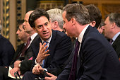 Leader of the Labour party Ed Miliband speaks with British Prime Minister David Cameron before listening to German Chancellor Angela Merkel...