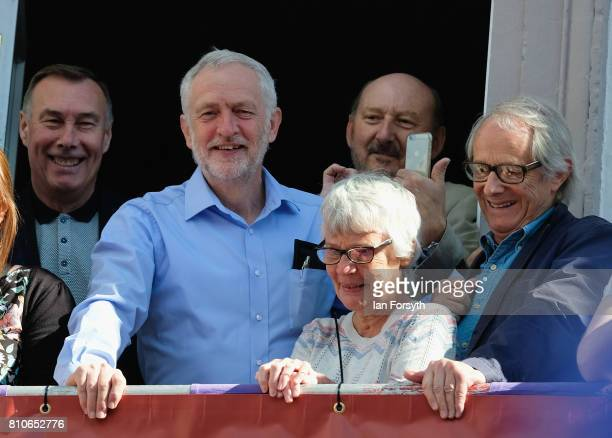 Leader of the Labour Party Jeremy Corbyn stands with film director Ken Loach as they watch colliery bands pass below the County Hotel balcony during...