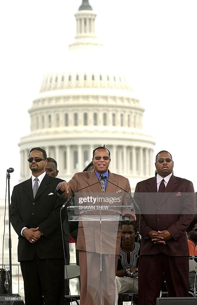 Leader of the Nation of Islam, Reverend Louis Farrakhan, flanked by body guards, speaks 17 August, 2002 during a rally for Reparations for Slavery on the National Mall in Washington, DC. Hundreds gathered on the Mall to demand that the US government compensate the Black community for slavery and discriminatory 19th century laws that stripped Blacks of many of the rights won in 1865. The rally was organized by a coalition of Black groups. AFP PHOTO Shawn THEW