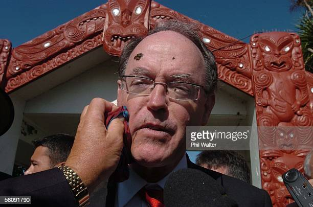 Leader of the National Party Don Brash has his face wiped clean after being hit in the face by mud thrown by a protestor at the entrance to Te Tii...