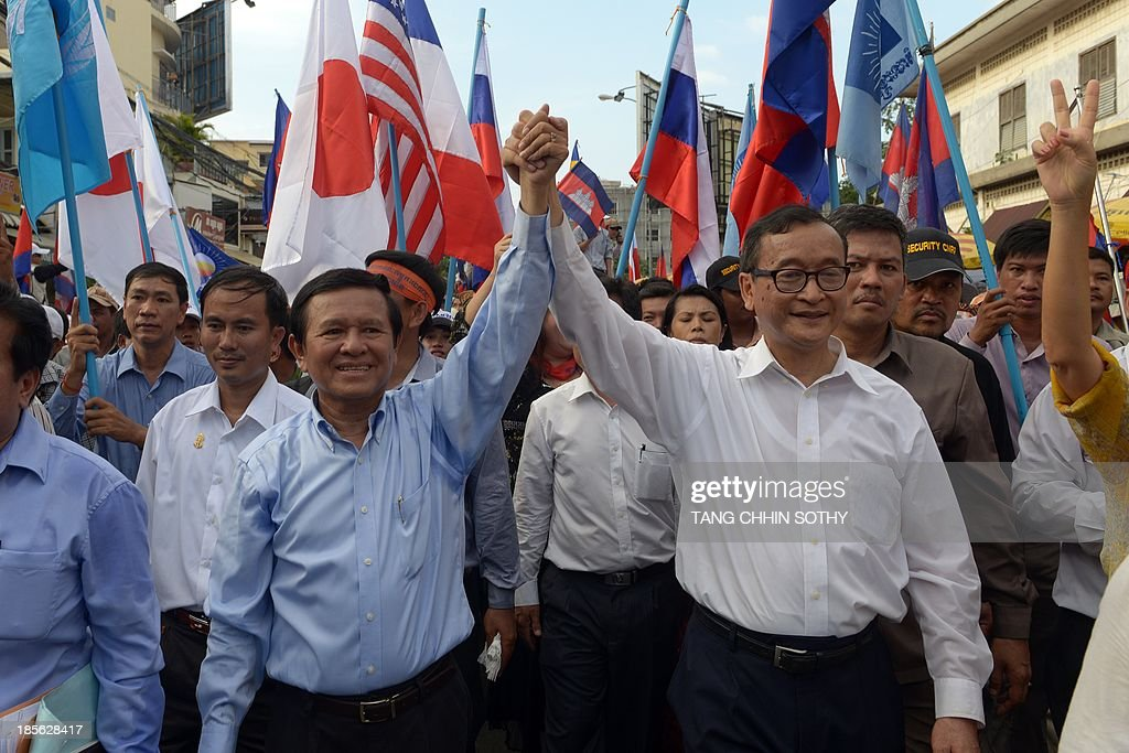Leader of the opposition Cambodia National Rescue Party (CNRP) Sam Rainsy (centre R) and deputy of CNRP Kem Sokha (centre L) raise their hands as they march during a demonstration in Phnom Penh on October 23, 2013. Thousands of Cambodia opposition supporters staged a demonstration amid high security on October 23, over fiercely disputed elections that extended strongman Prime Minister Hun Sen's nearly three-decade rule, following bloody protests last month.