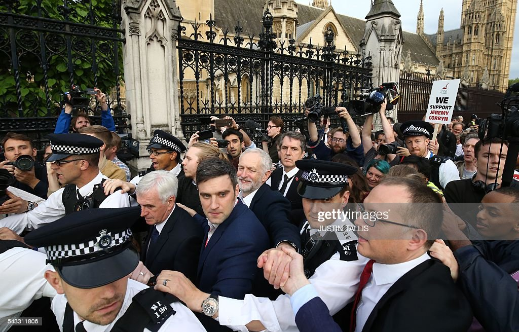 Leader of the opposition Labour Party Jeremy Corbyn (C) reaches out to a supporters as he leaves after delivering a speech outside parliament during a pro-Corbyn demonstration in central London on June 27, 2016. Britain's historic decision to leave the 28-nation bloc has sent shockwaves through the political and economic fabric of the nation. It has also fuelled fears of a break-up of the United Kingdom with Scotland eyeing a new independence poll, and created turmoil in the opposition Labour party where leader Jeremy Corbyn is battling an all-out revolt. TALLIS