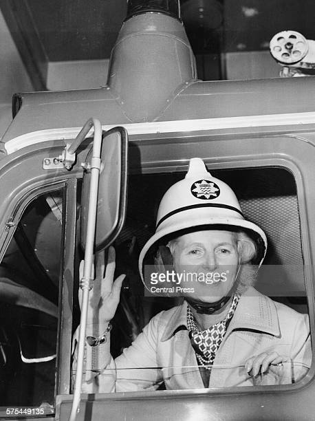 Leader of the Opposition Margaret Thatcher wearing a fireman's helmet as she waves from the cab of a fire engine during a visit to Finchley Fire...