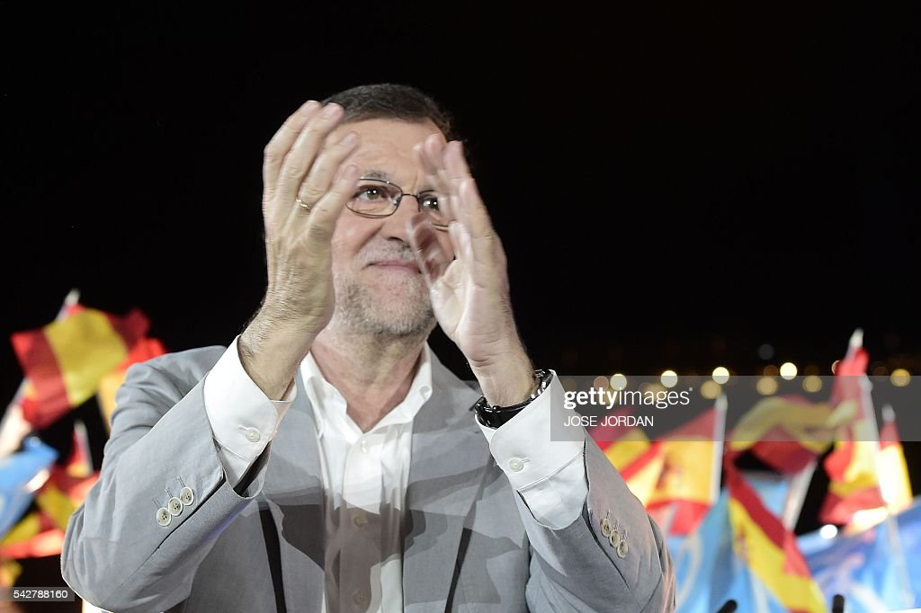 Leader of the Popular Party (PP) and Spain's caretaker Prime Minister and party candidate, Mariano Rajoy claps on arrival to the partys final campaign meeting in Madrid on June 24, 2016 ahead of the June 26 general election. Spain votes again on June 26, six months after an inconclusive election which saw parties unable to agree on a coalition government. JORDAN