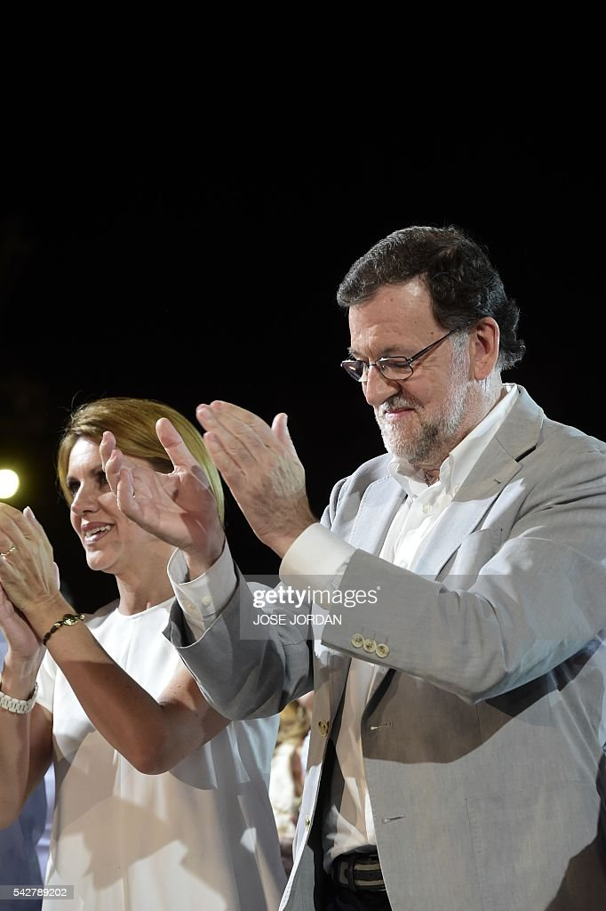 Leader of the Popular Party (PP) and Spain's caretaker Prime Minister and party candidate, Mariano Rajoy (C) claps on arrival to the partys final campaign meeting in Madrid on June 24, 2016 ahead of the June 26 general election. Spain votes again on June 26, six months after an inconclusive election which saw parties unable to agree on a coalition government. JORDAN