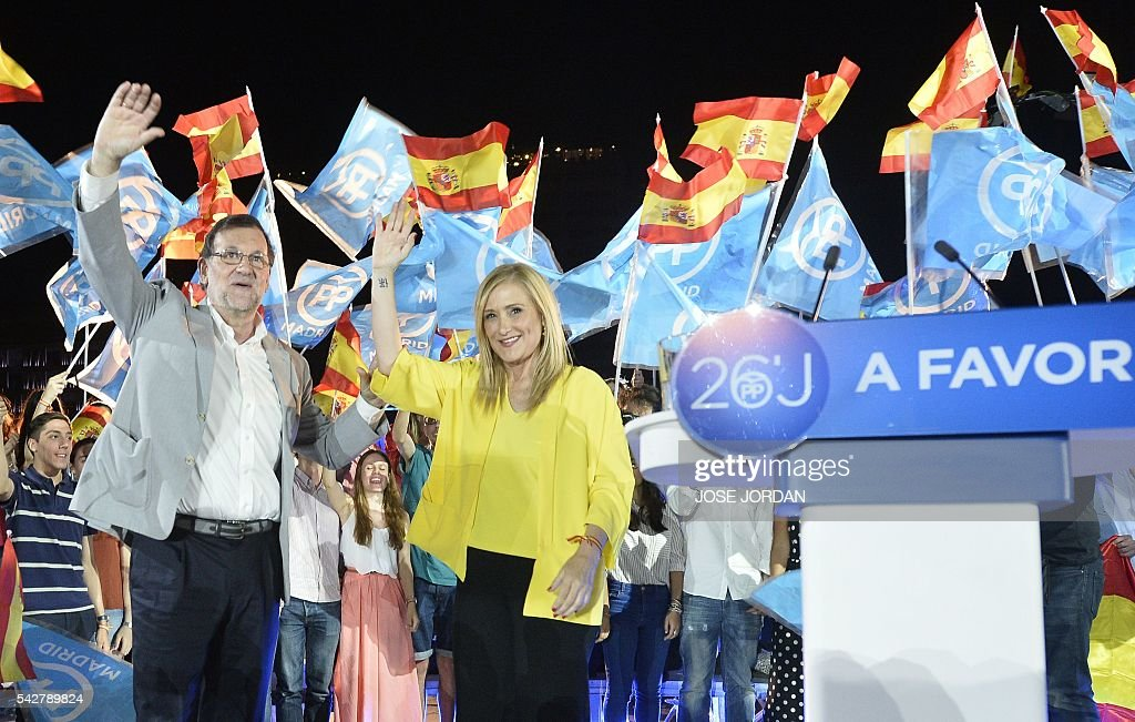 Leader of the Popular Party (PP) and Spain's caretaker Prime Minister and party candidate, Mariano Rajoy (L) and Spain's conservative Popular Party (PP) member Cristina Cifuentes wave on arrival to the partys final campaign meeting in Madrid on June 24, 2016 ahead of the June 26 general election. Spain votes again on June 26, six months after an inconclusive election which saw parties unable to agree on a coalition government. JORDAN