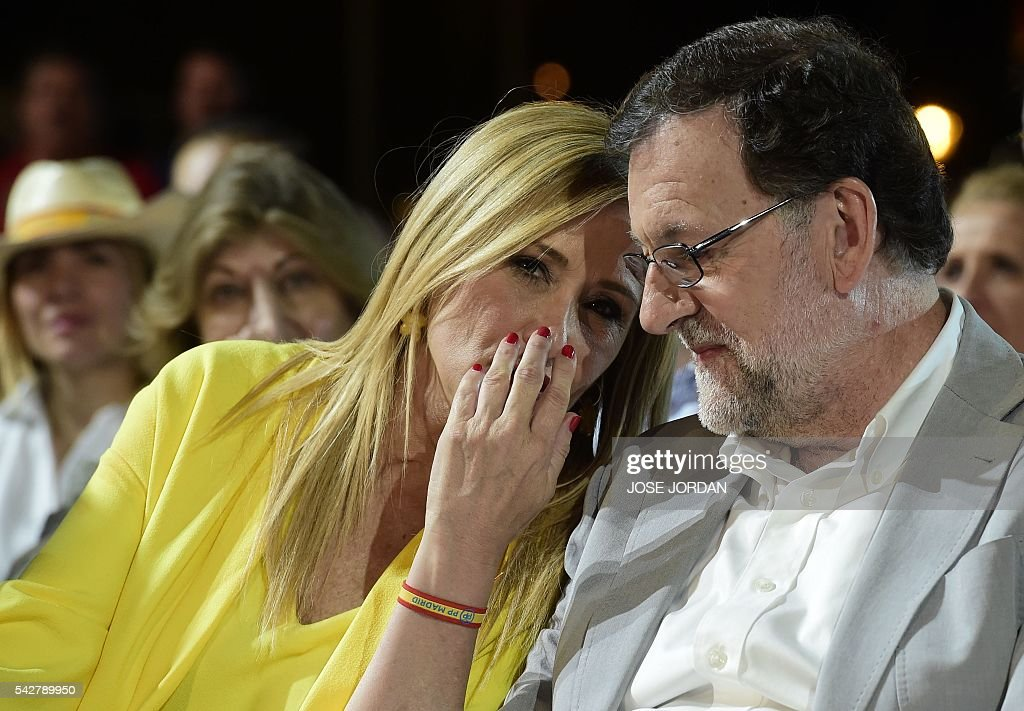Leader of the Popular Party (PP) and Spain's caretaker Prime Minister and party candidate, Mariano Rajoy (R) and Spain's conservative Popular Party (PP) member Cristina Cifuentes chat during the partys final campaign meeting in Madrid on June 24, 2016 ahead of the June 26 general election. Spain votes again on June 26, six months after an inconclusive election which saw parties unable to agree on a coalition government. JORDAN