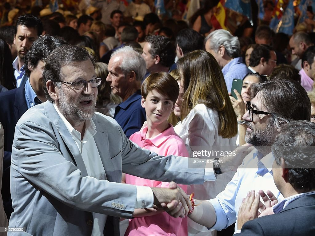 Leader of the Popular Party (PP) and Spain's caretaker Prime Minister and party candidate, Mariano Rajoy shakes hands as he walks through the crowd on arrival to the partys final campaign meeting in Madrid on June 24, 2016 ahead of the June 26 general election. Spain votes again on June 26, six months after an inconclusive election which saw parties unable to agree on a coalition government. JORDAN