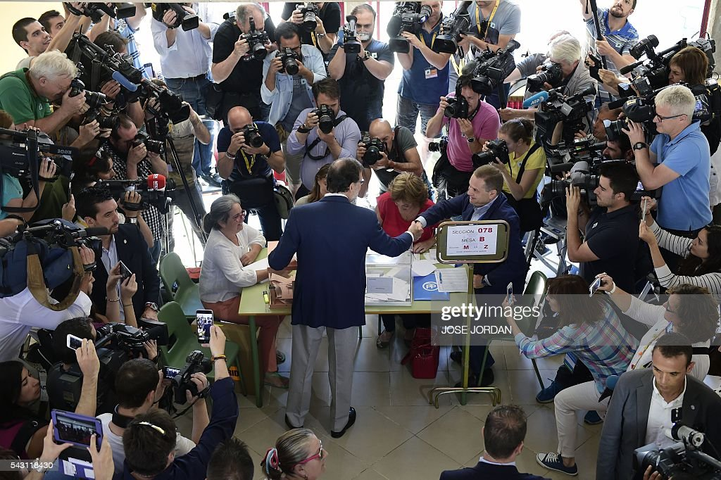 Leader of the Popular Party (PP) and Spain's caretaker Prime Minister and party candidate, Mariano Rajoy (C), shakes hands with a scrutineer before voting in Spains general election at the Bernadette college polling station in Moncloa-Aravaca, Madrid, on June 26, 2016. Spain votes today, six months after an inconclusive election which saw parties unable to agree on a coalition government. JORDAN