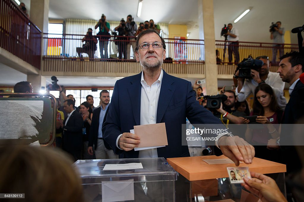 Leader of the Popular Party (PP) and Spain's caretaker Prime Minister and party candidate, Mariano Rajoy, presents his personal identification (DNI) to vote in Spains general election at the Bernadette college polling station in Moncloa-Aravaca, Madrid, on June 26, 2016. Spain votes today, six months after an inconclusive election which saw parties unable to agree on a coalition government. MANSO
