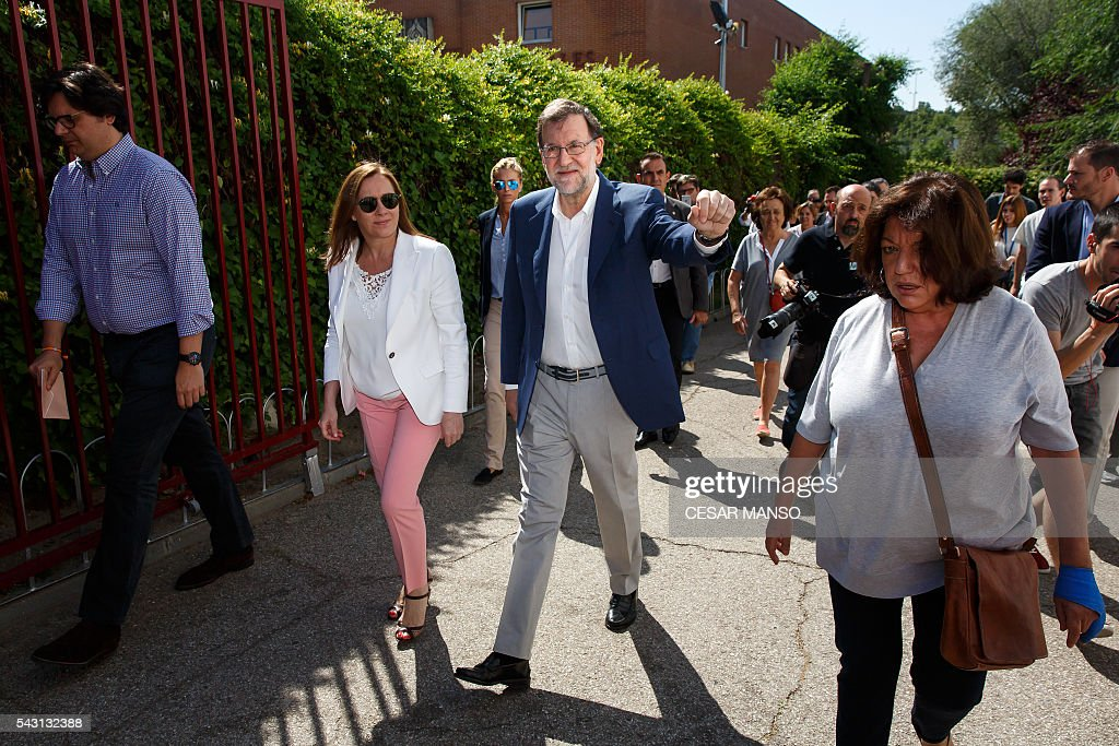 Leader of the Popular Party (PP) and Spain's caretaker Prime Minister and party candidate, Mariano Rajoy, (C) and his wife, Elvira Fernandez arrives to vote in Spains general election at the Bernadette college polling station in Moncloa-Aravaca, Madrid, on June 26, 2016. Spain votes today, six months after an inconclusive election which saw parties unable to agree on a coalition government. MANSO