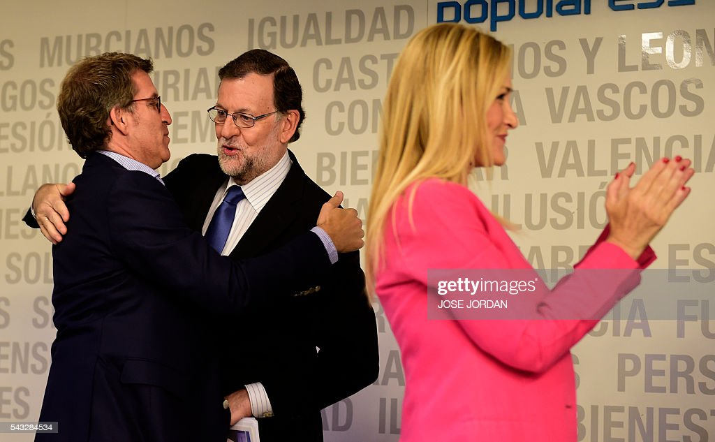 Leader of the Popular Party (PP) and Spain's caretaker Prime Minister, Mariano Rajoy (C) is congratulate by Galician regional president Alberto Nunez Feijoo during a meeting of the national executive committee held one day after the Spanish general elections, at the PP headquarters in Madrid, on Juny 27, 2016. Spain hoped on June 27 that repeat weekend elections would unblock the country's political paralysis after the conservatives came out strengthened with more seats, although they still face resistance from hostile rivals. / AFP / JOSE