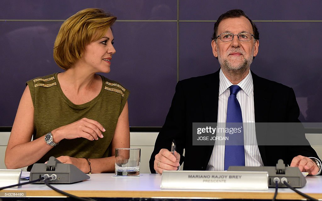 Leader of the Popular Party (PP) and Spain's caretaker Prime Minister, Mariano Rajoy (R) looks on next to General Secretary of Popular Party (PP) Maria Dolores de Cospedal during a meeting of the national executive committee held one day after the Spanish general elections, at the PP headquarters in Madrid, on Juny 27, 2016. Spain hoped on June 27 that repeat weekend elections would unblock the country's political paralysis after the conservatives came out strengthened with more seats, although they still face resistance from hostile rivals. / AFP / JOSE