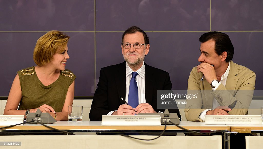 Leader of the Popular Party (PP) and Spain's caretaker Prime Minister, Mariano Rajoy (C) smiles between General Secretary of Popular Party (PP) Maria Dolores de Cospedal (L) and Deputy Secretary of Organization of the PP, Fernando Martinez Maillo during a meeting of the national executive committee held one day after the Spanish general elections, at the PP headquarters in Madrid, on Juny 27, 2016. Spain hoped on June 27 that repeat weekend elections would unblock the country's political paralysis after the conservatives came out strengthened with more seats, although they still face resistance from hostile rivals. / AFP / JOSE