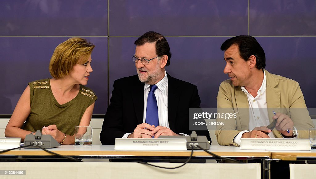 Leader of the Popular Party (PP) and Spain's caretaker Prime Minister, Mariano Rajoy (C) speaks with General Secretary of Popular Party (PP) Maria Dolores de Cospedal (L) and Deputy Secretary of Organization of the PP, Fernando Martinez Maillo during a meeting of the national executive committee held one day after the Spanish general elections, at the PP headquarters in Madrid, on Juny 27, 2016. Spain hoped on June 27 that repeat weekend elections would unblock the country's political paralysis after the conservatives came out strengthened with more seats, although they still face resistance from hostile rivals. / AFP / JOSE