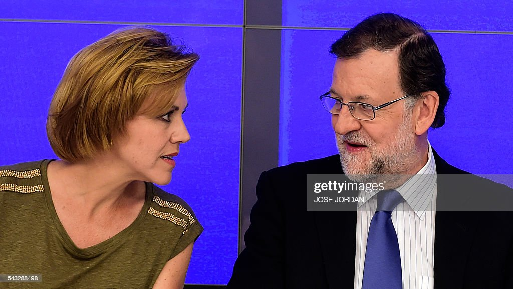 Leader of the Popular Party (PP) and Spain's caretaker Prime Minister, Mariano Rajoy (R) looks speaks with General Secretary of Popular Party (PP) Maria Dolores de Cospedal, during a meeting of the national executive committee held one day after the Spanish general elections, at the PP headquarters in Madrid, on June 27, 2016. Spain hoped on June 27 that repeat weekend elections would unblock the country's political paralysis after the conservatives came out strengthened with more seats, although they still face resistance from hostile rivals. / AFP / JOSE