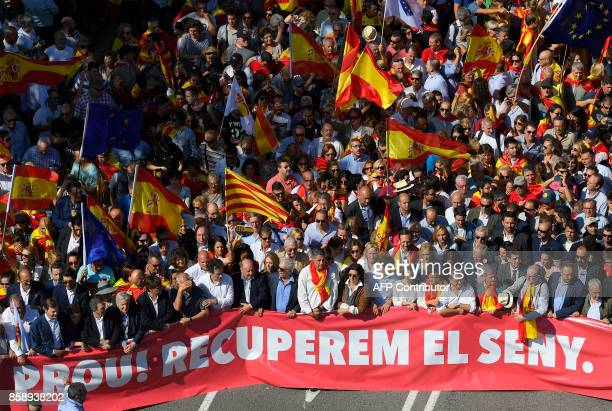 Leader of the Popular Party of Catalonia Xavier Garcia Albiol and Peruvian writer Mario Vargas Llosa walk behind a banner reading in Catalan 'Enough...