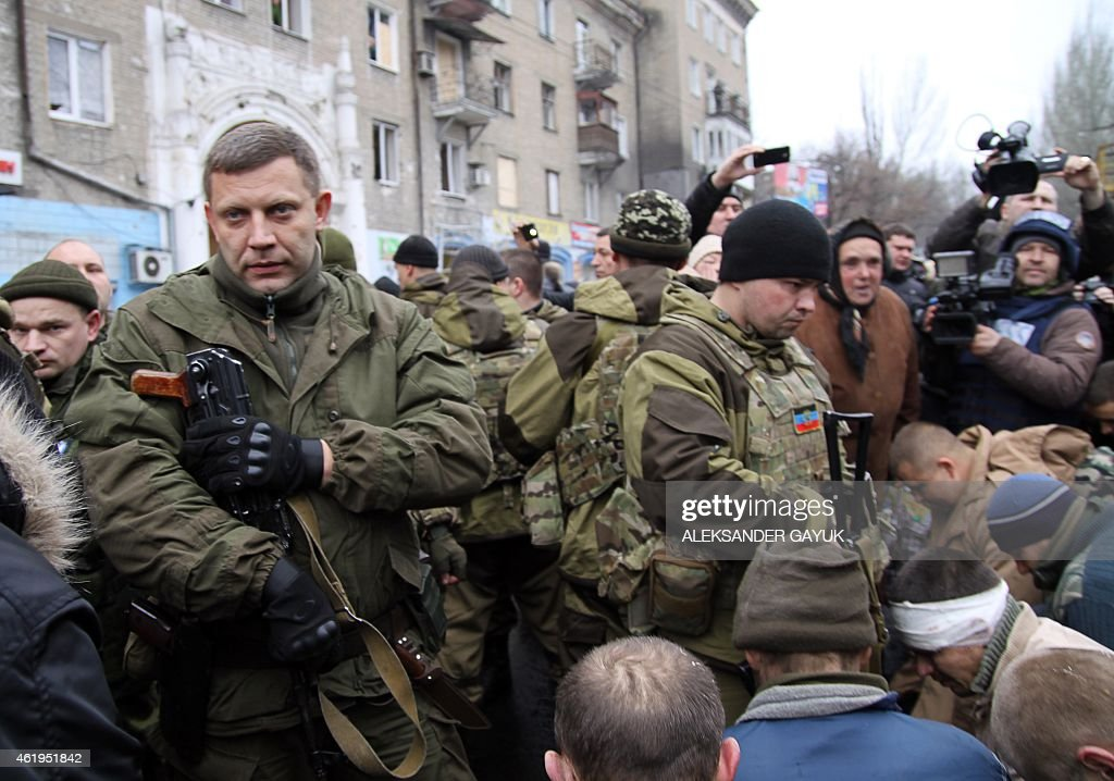 Leader of the selfdeclared Donetsk People's Republic Alexander Zakharchenko stands next to kneeling captive Ukrainian soldiers at a bus stop where 13...