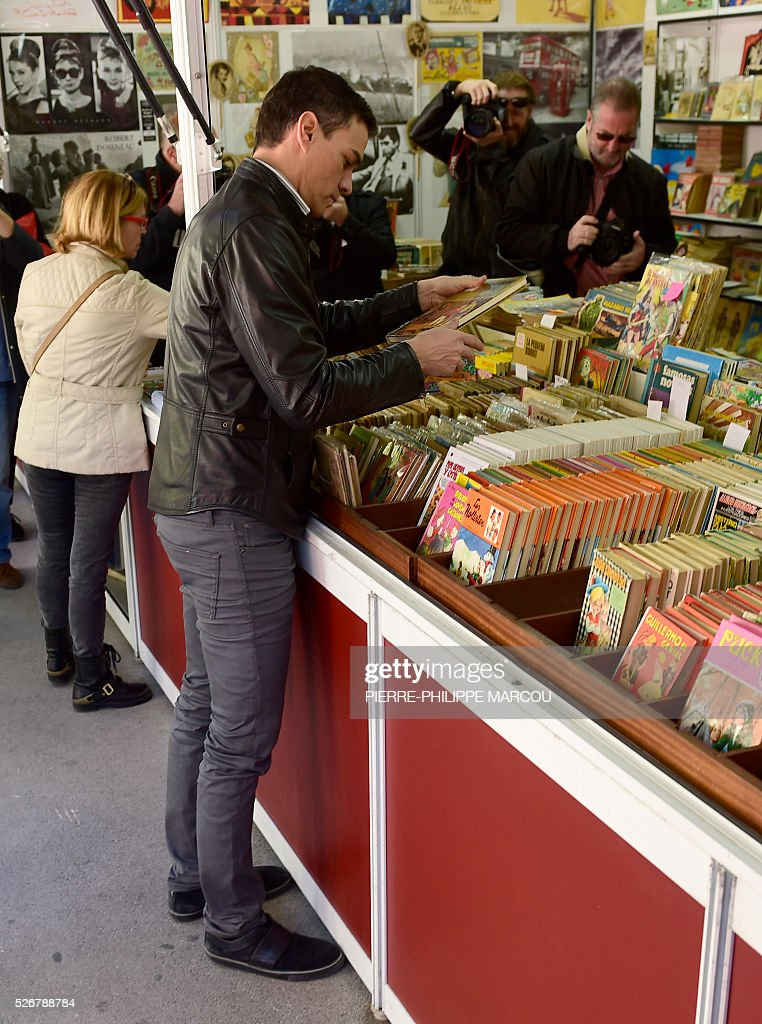 Leader of the Socialist Party (PSOE) Pedro Sanchez checks boooks at the Old Books Fair before to take part to the traditional May Day rally in Madrid on May 1, 2016. / AFP / PIERRE