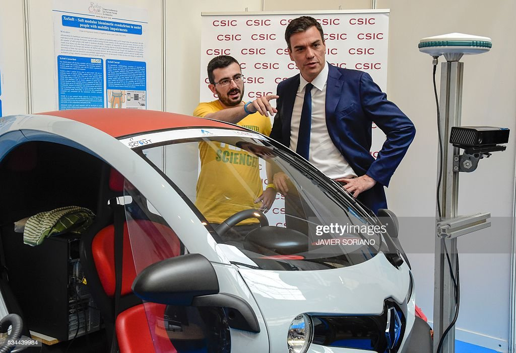 Leader of the Spanish Socialist Party (PSOE) Pedro Sanchez stands past a car as he visits a Robotic Fair after presenting the document 'Yes to the six principles for the Government of Change' in Madrid on May 26, 2016. / AFP / JAVIER