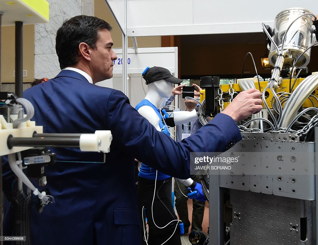 Leader of the Spanish Socialist Party (PSOE) Pedro Sanchez visits a Robotic Fair after presenting the document 'Yes to the six principles for the Government of Change' in Madrid on May 26, 2016. / AFP / JAVIER
