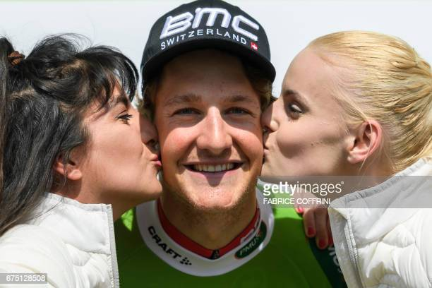 Leader of the sprint ranking Switzerland's Stefan Kueng of team BMC is kissed by hostesses during the podium ceremony after competing in the last...