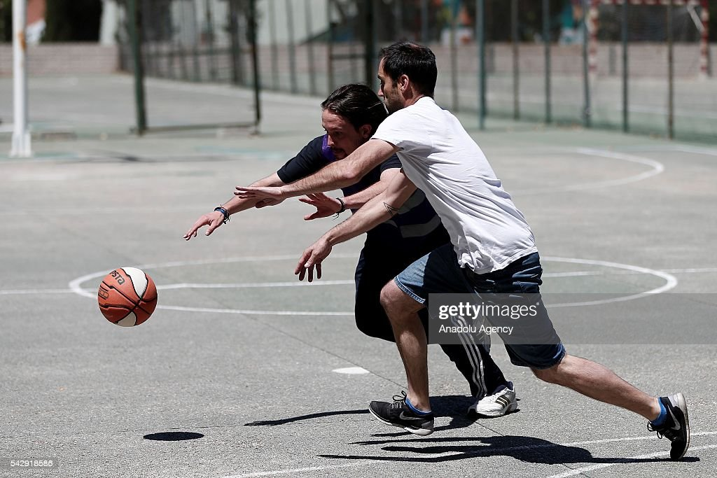 Leader of the Unidos Podemos 'United We Can', Pablo Iglesias (L) plays basketball with his friend ahead of Spanish General Elections in Madrid, Spain on June 25, 2016.
