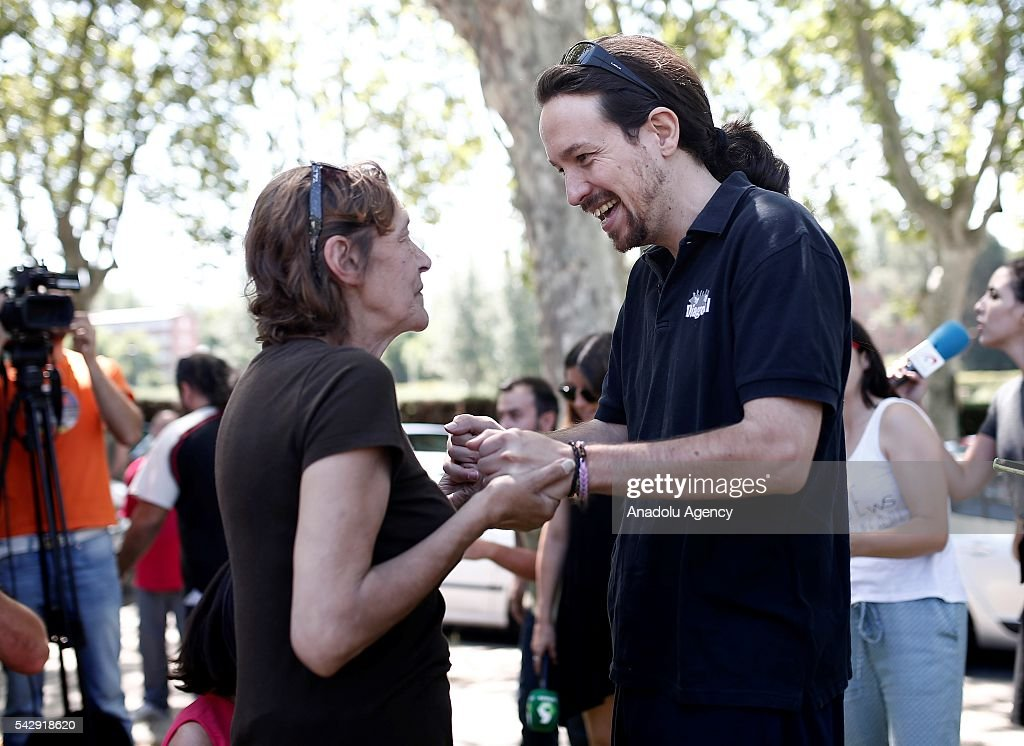 Leader of the Unidos Podemos 'United We Can', Pablo Iglesias (R) talks with a woman as he comes to play basketball with his friends ahead of Spanish General Elections in Madrid, Spain on June 25, 2016.