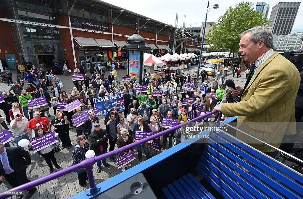 Leader of the United Kingdom Independence Party (UKIP) Nigel Farage (R) addresses supporters from atop his tour bus in Birmingham, central England, on May 31, 2016, during an anti-EU campaign event ahead of the forthcoming EU referendum. Politicians and world leaders have dominated the headlines in the campaign for Britain's Jun 23, 2016 EU referendum, but a passionate battle for the country's future is also being fought by activists on the streets. / AFP / PAUL