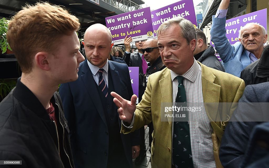 Leader of the United Kingdom Independence Party (UKIP) Nigel Farage (2R) gestures as he is confronted by Luke Holland (L) whilst campaigning to leave the European Union during a stop on his anti-EU bus tour, in Birmingham, central England, on May 31, 2016, ahead of Britain's forthcoming EU referendum. Politicians and world leaders have dominated the headlines in the campaign for Britain's Jun 23, 2016 EU referendum, but a passionate battle for the country's future is also being fought by activists on the streets. / AFP / PAUL