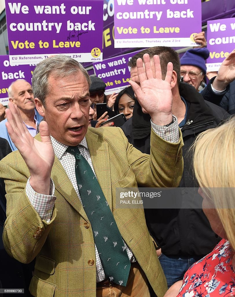 Leader of the United Kingdom Independence Party (UKIP) Nigel Farage (L) gestures whilst campaigning to leave the European Union during a stop on his anti-EU bus tour, in Birmingham, central England, on May 31, 2016, ahead of Britain's forthcoming EU referendum. Politicians and world leaders have dominated the headlines in the campaign for Britain's Jun 23, 2016 EU referendum, but a passionate battle for the country's future is also being fought by activists on the streets. / AFP / PAUL