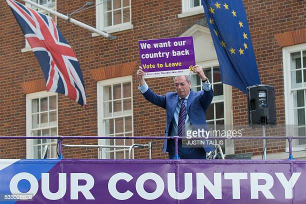 Leader of the United Kingdom Independence Party Nigel Farage holds up a placard as he poses for photographers at the launch of the party's opentop...