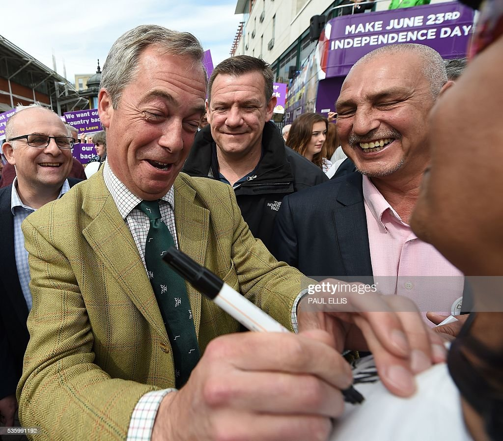 Leader of the United Kingdom Independence Party (UKIP) Nigel Farage (2L) reacts as he signs the T-shirt of a supporter whilst campaigning to leave the European Union during a stop on his anti-EU bus tour, in Birmingham, central England, on May 31, 2016, ahead of Britain's forthcoming EU referendum. Politicians and world leaders have dominated the headlines in the campaign for Britain's Jun 23, 2016 EU referendum, but a passionate battle for the country's future is also being fought by activists on the streets. / AFP / PAUL