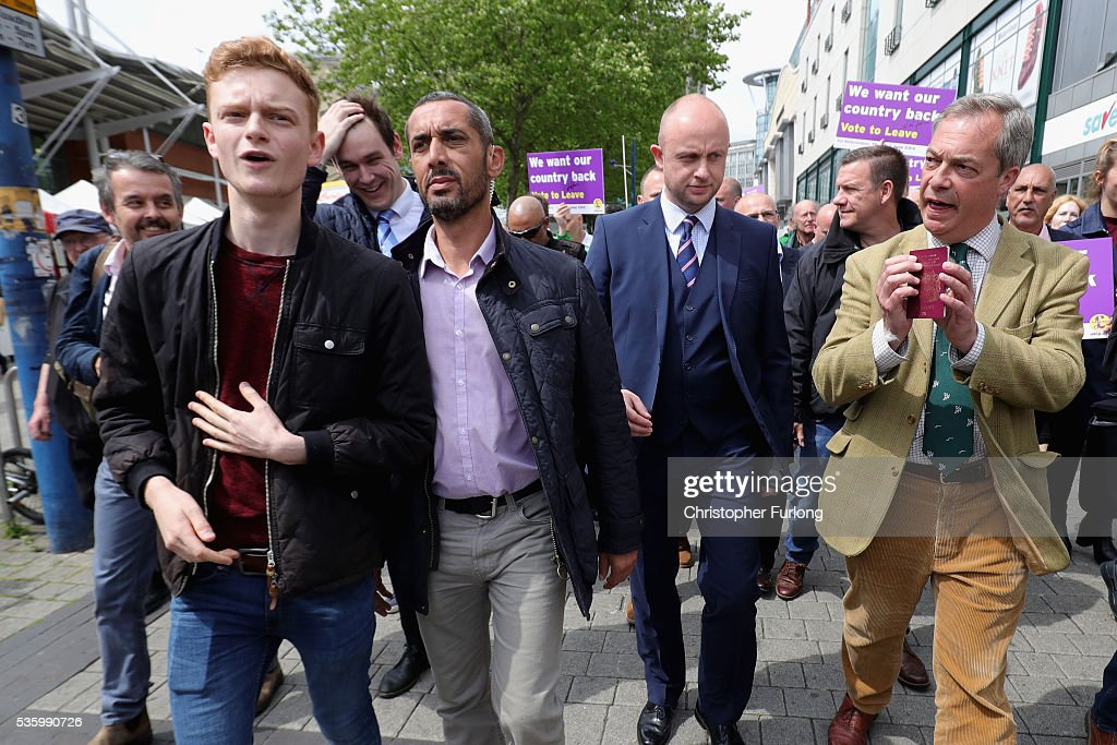 Leader of the United Kingdom Independence Party (UKIP), Nigel Farage, shows his European passport to EU In supporter Luke Holland (L) as he tours Birmingham Rag Market during campaigning for votes to leave the European Union in the referendum on May 31, 2016 in Birmingham, England. With 23 days to go until the EU referendum, Nigel Farage took his battle bus to Birmingham encouraging British people to vote to leave the EU on 23rd June 2016.
