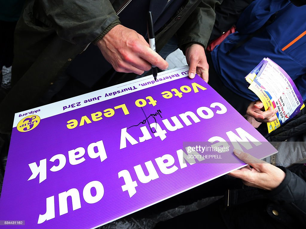 Leader of the United Kingdom Independence Party (UKIP), Nigel Farage signs his name on a supporter's placard as he canvasses for supporters whilst campaigning to leave the European Union, ahead of the June 23 referendum, in Newcastle upon Tyne, north-east England on May 26, 2016. A series of recent polls suggest a widening lead for supporters of Britain's continued European Union membership, handing 'Remain' campaigners a psychological boost, before the country votes in a crucial in-out referendum on June 23. / AFP / SCOTT
