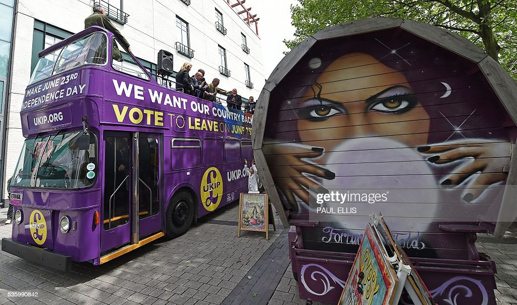 Leader of the United Kingdom Independence Party (UKIP) Nigel Farage (C) waves from atop his tour bus as it passes a fortune tellers stall in Birmingham, central England, on May 31, 2016, during an anti-EU campaign event ahead of the forthcoming referendum. Politicians and world leaders have dominated the headlines in the campaign for Britain's Jun 23, 2016 EU referendum, but a passionate battle for the country's future is also being fought by activists on the streets. / AFP / PAUL