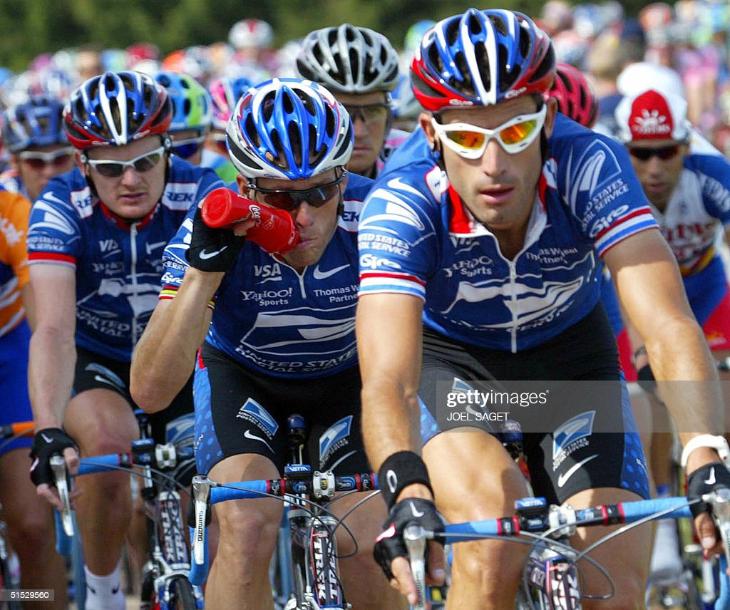 leader of the US Postal Service team, US Lance Armstrong (C) drinks as he rides surrounded with his teammates and compatriots Floyd Landis (L) and George Hincapie, during the sunny 2nd stage of the 89th Tour de France between Luxembourg and Sarrebrucken, 08 July 2002.