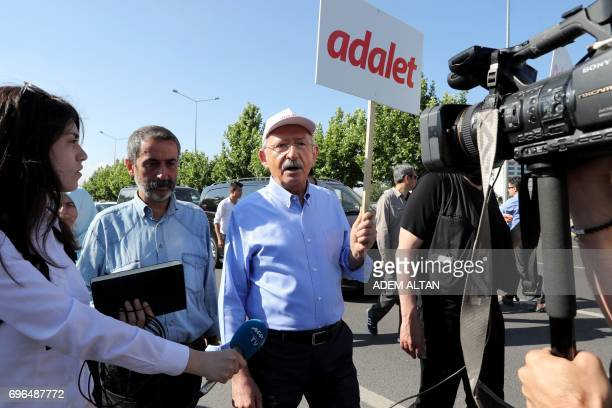 Leader of Turkey's main opposition Republican People's Party Kemal Kilicdaroglu gives an interview as he walks with a placard reading 'Justice'...