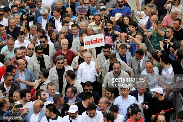 TOPSHOT Leader of Turkey's main opposition Republican People's Party Kemal Kilicdaroglu walks with placard reading 'Justice' during a protest march...