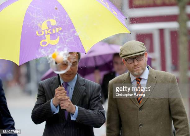 UKIP leader Paul Nuttall and former Leader Nigel Farage MEP dodge an egg thrown by a youth as they arrive in StokeOnTrent for a public meeting this...
