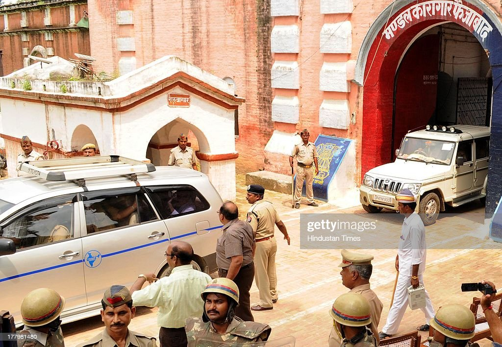 VHP leader Praveen Togadia waves from inside the car as he is moved from Faizabad district jail to Etah under tight police security on August 26, 2013 in Faizabad, India. Togadiya was detained in wake of Vishwa Hindu Parishad's (VHP) 84 Kosi yatra, which was banned by Uttar Pradesh government.