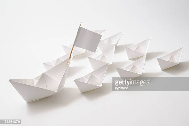 Leader ship of white paper boats fleet on white background