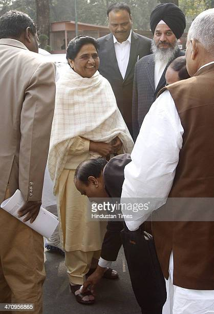 BSP leader touching feet of BSP supremo Mayawati as she arrives at Parliament House on last day of 15th Lok Sabha on February 21 2014 in New Delhi...