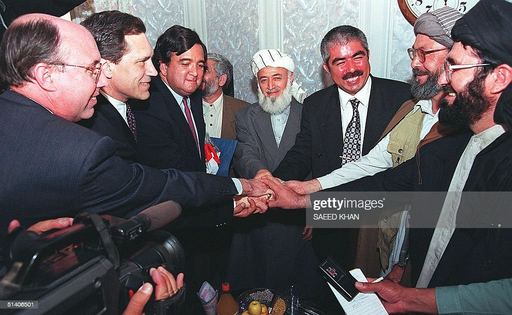 Leaders of Afghan opposition alliance and United States delegation for mediation join hands after their 90minute talks in Shiberghan northern...
