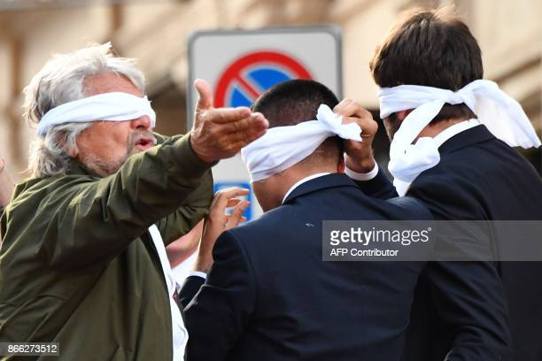 Leaders of the antiestablishment Five Star Movement Beppe Grillo Luigi Di Maio and Alessandro Di Battista cover their eyes with a white scraf during...