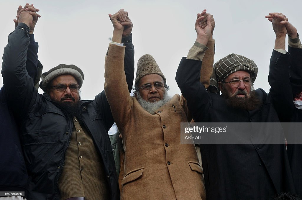 Leaders of the Defence of Pakistan Council (L) Hafiz Saeed, Munawar Hasan (C) and Moulana Sami ul Haq (R) raise their hands in a rally to mark a Kashmir Solidarity day in Lahore on February 5, 2013. Pakistan observed Kashmir Solidarity Day on February 5, to denounce Indian rule in the disputed Himalayan region claimed in whole by both countries. AFP PHOTO/Arif ALI