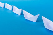 Business Leadership Concept - White Colored Paper ship Origami leading the rest of the white paper ships on blue background.